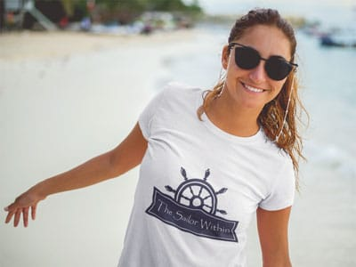 Brown haired girl at the beach with the The Sailor Within Logo T-Shirt